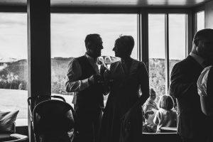 Das glückliche Hochzeitspaar in tiefem Blickkontakt am Panoramafenster