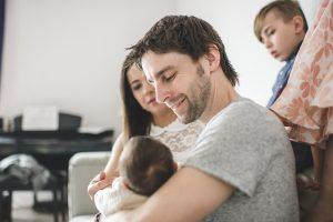 Papa mit neugeboren Baby zu Hause